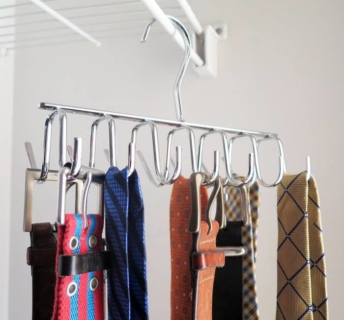 the rack with 14 small hooks hanging in a closet and holding belts and ties