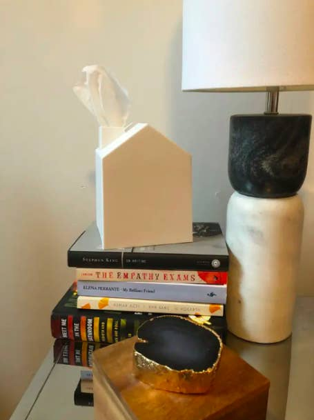 house-shaped white square tissue box cover on a stack of books