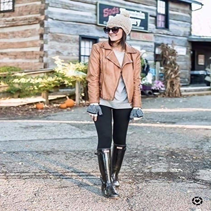 Model wearing the black leggings with rain boots and leather jacket.