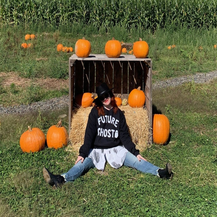 a buzzfeed writer in a pumpkin patch wearing the sweatshirt