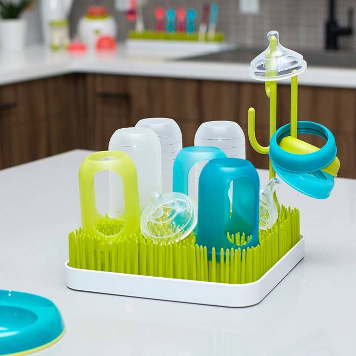 A dish mat with tall thin silicone sticks on it A cactus-shaped silicone hook sticks up in the middle