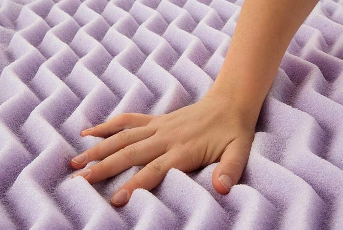 A person pressing their hand against the mattress topper to show how soft it is