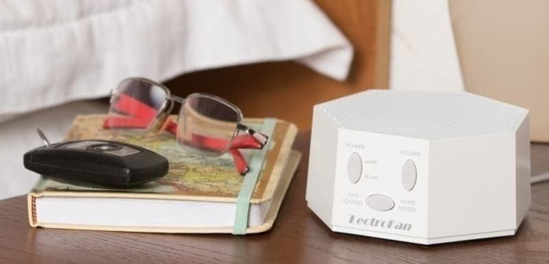 The white noise sound machine in white on a night stand