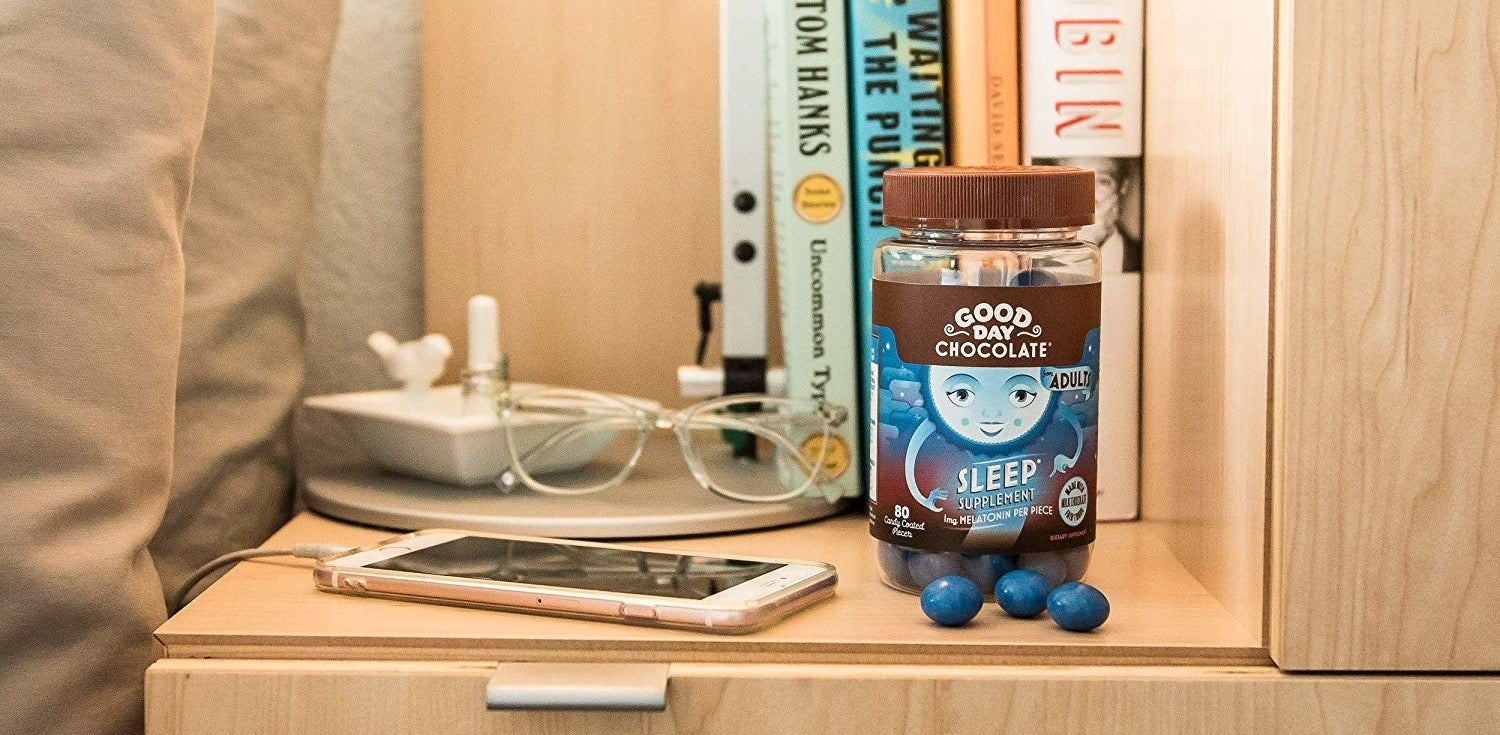The container of the chocolate sleep supplement next to a bed