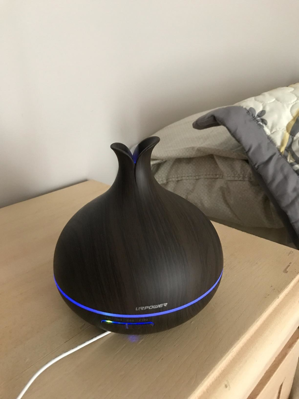A reviewer showing the diffuser which is round on the bottom and has a narrow opening on top to emit steam