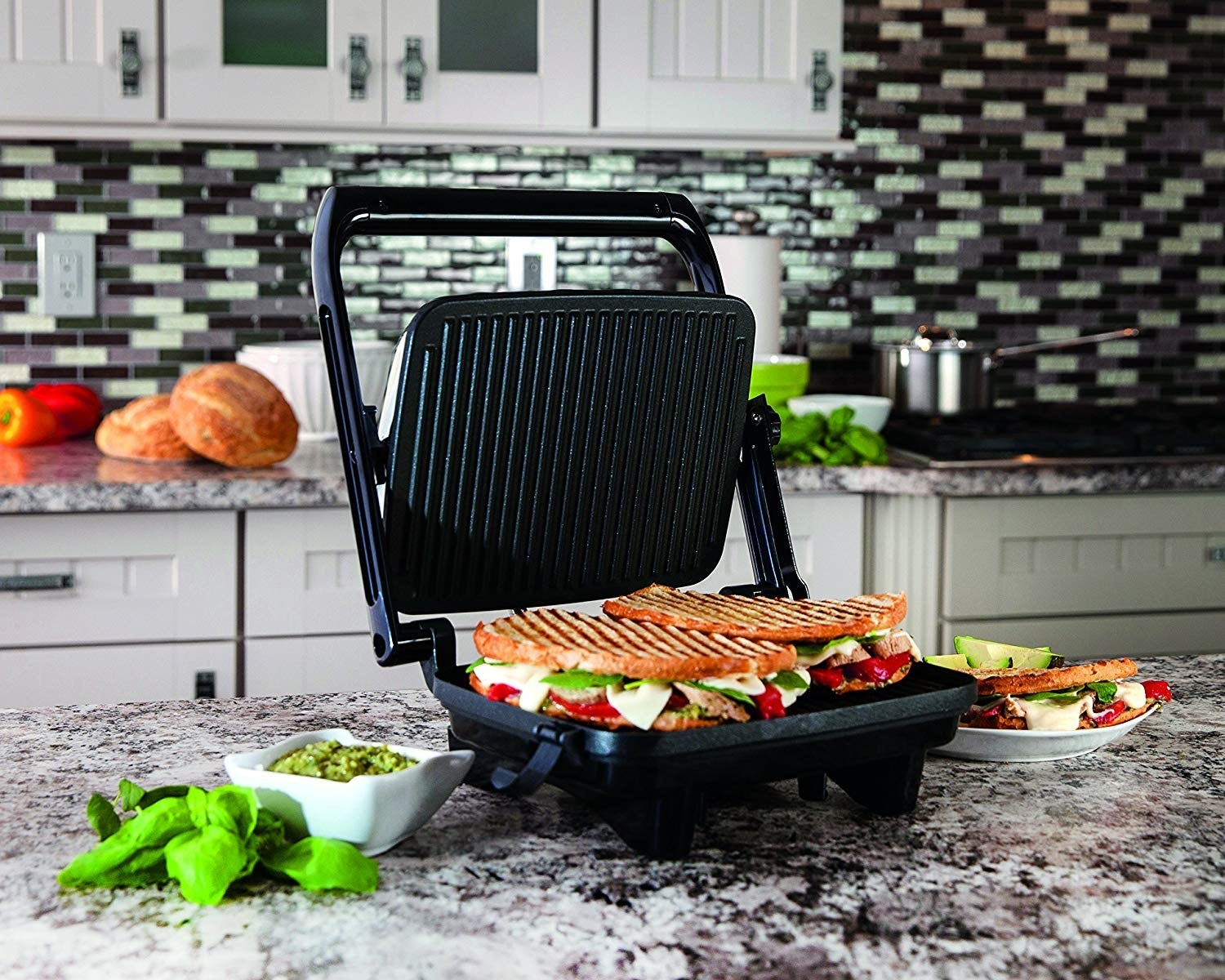 The hinged panini press with a sandwich with grill marks inside