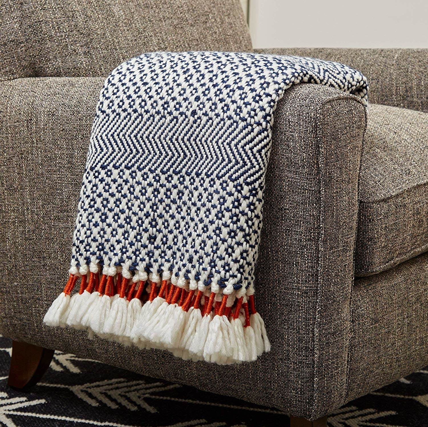 Knitted throw blanket with decorative fringe on the ends