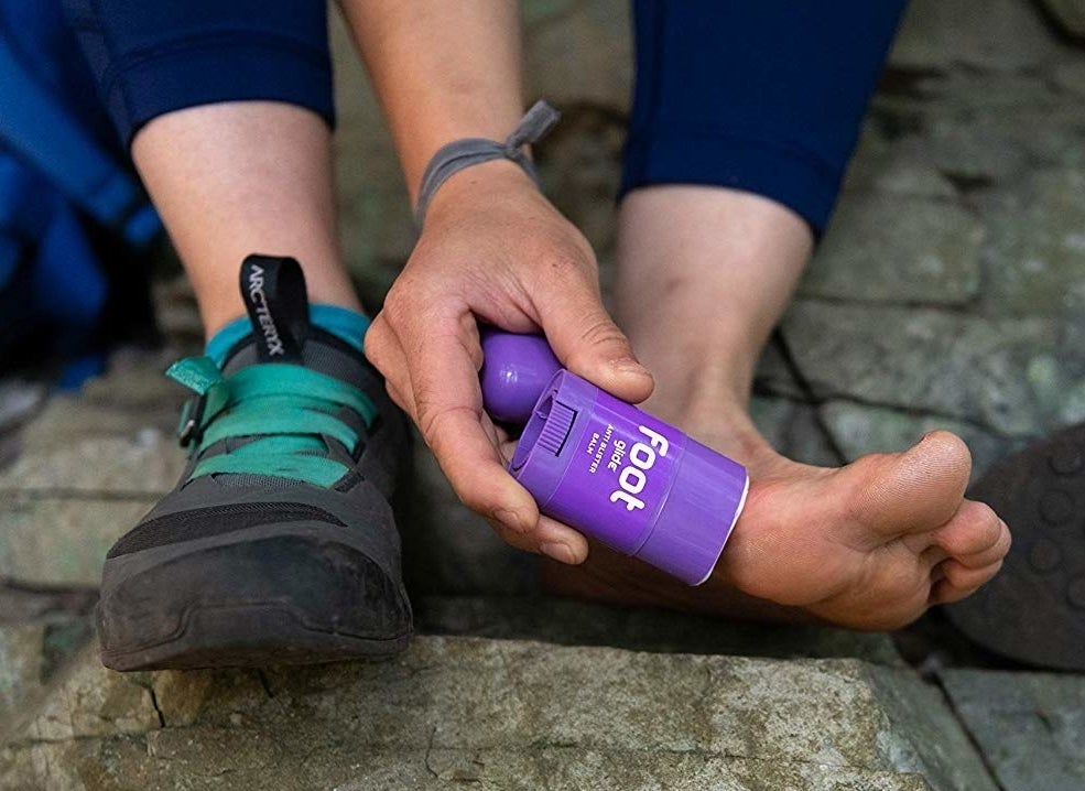 A person applying the tube of blister balm to their bare foot