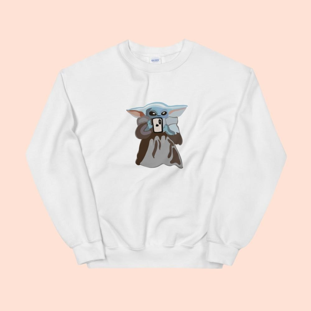 a white sweatshirt with baby yoda on it taking a selfie