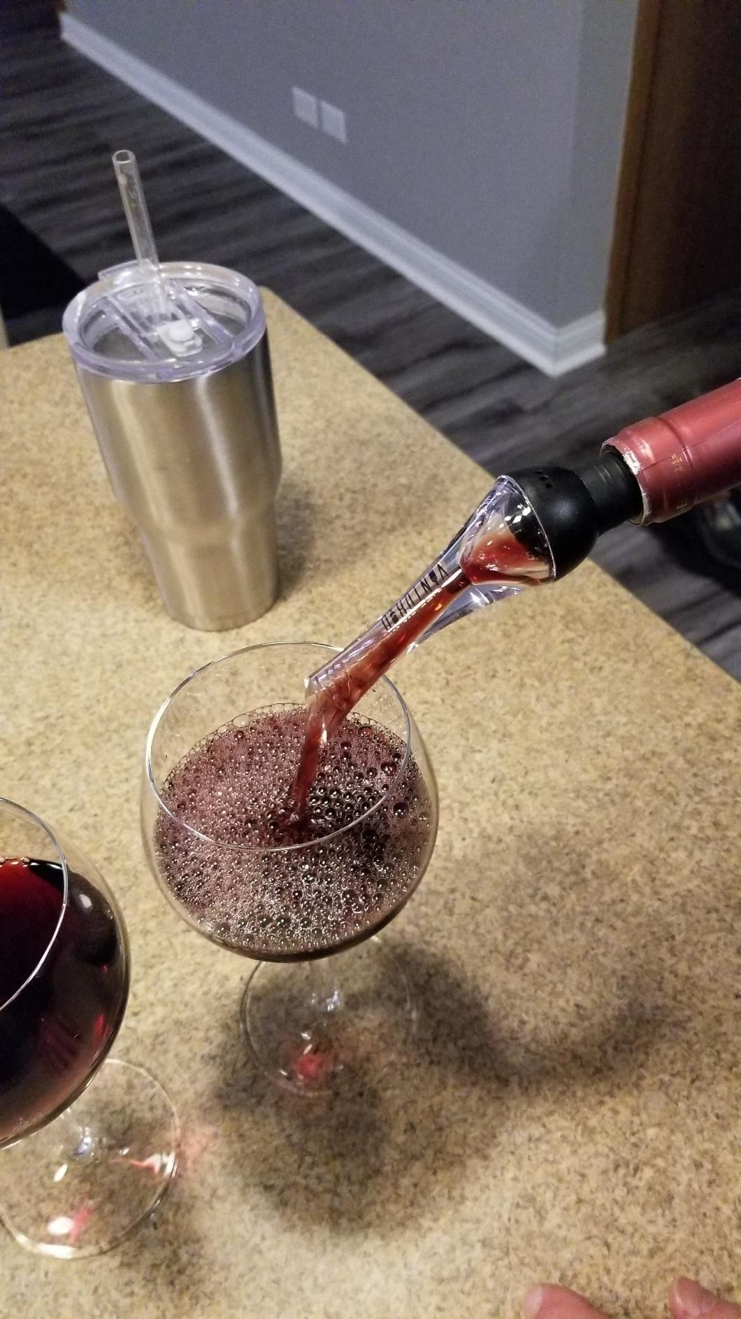 A reviewer using the chute-like attachment to pour a glass of wine