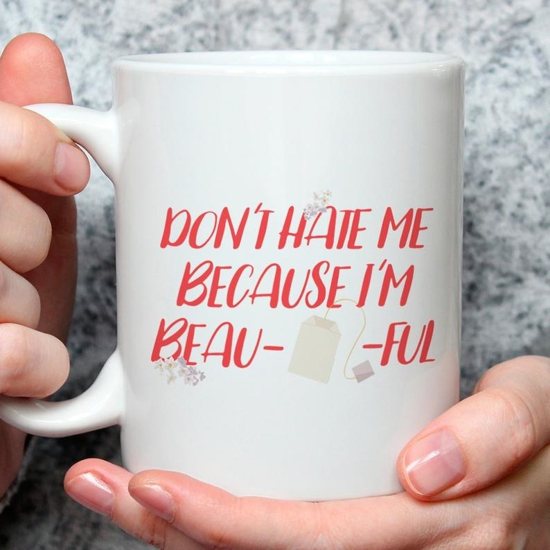 "A ceramic mug that reads, ""Don't Hate Me Because I'm Beau-TEA-ful."""