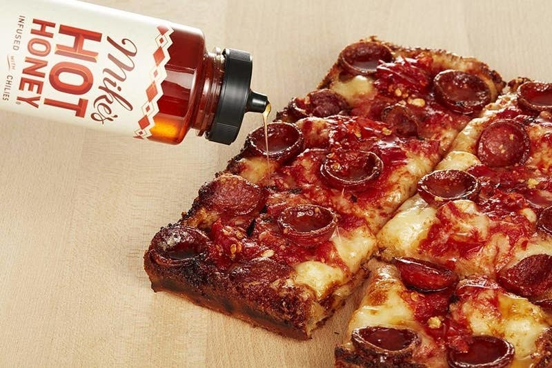 Bottle of honey pouring on a pepperoni pizza