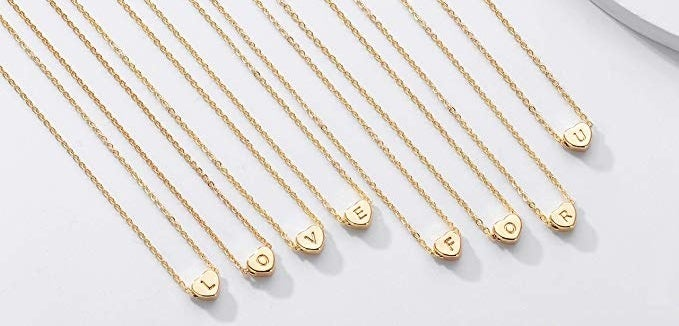 an array of the thin gold necklaces with gold hearts with initials in it