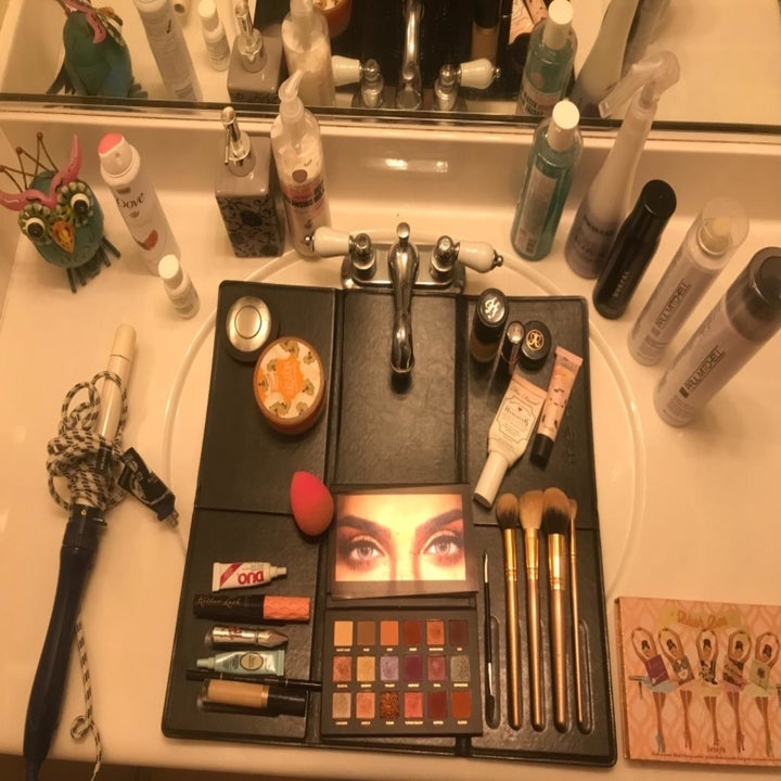 The makeup mat spread over the sink with all the makeup neatly arranged on it