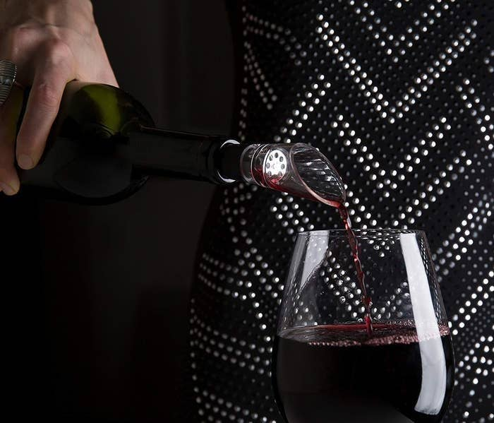 model pouring a glass of wine with the aerator on the bottle