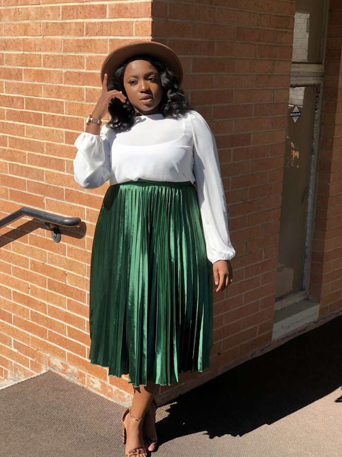 A reviewer wearing the pleated skirt in green