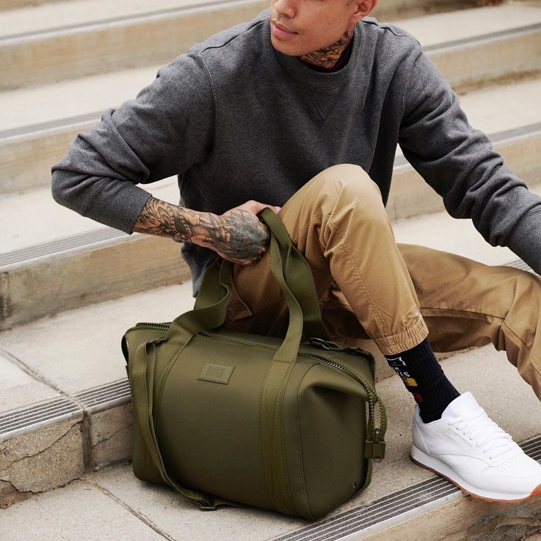 A model holding the army green duffel
