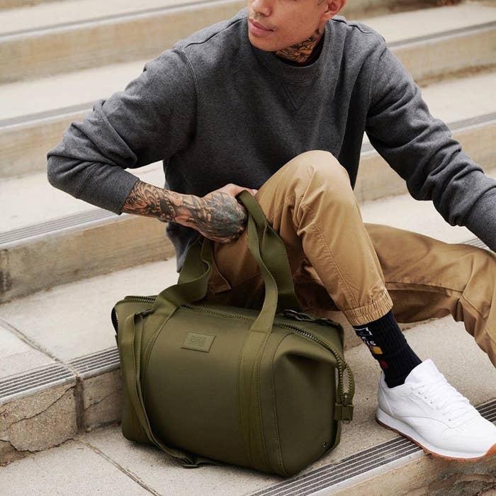 model holding a green dagne dover bag