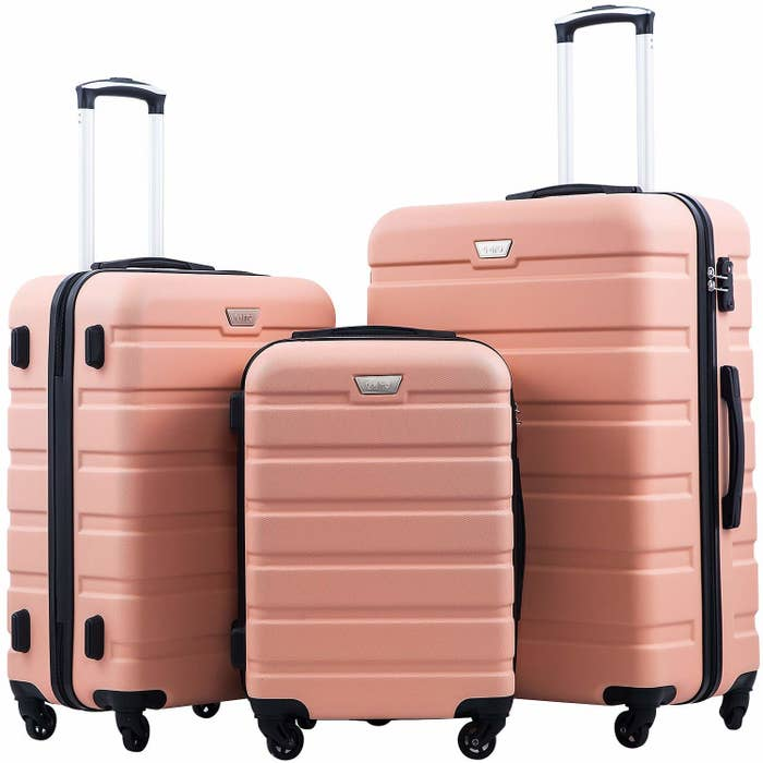 Three pink hard shell suitcases in small, medium, and large