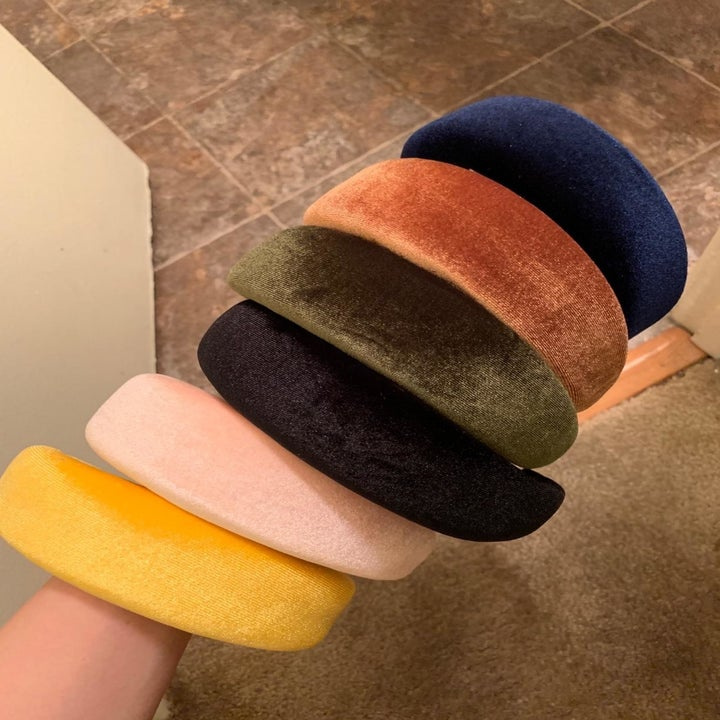 A reviewer holding the headbands in six color varieties