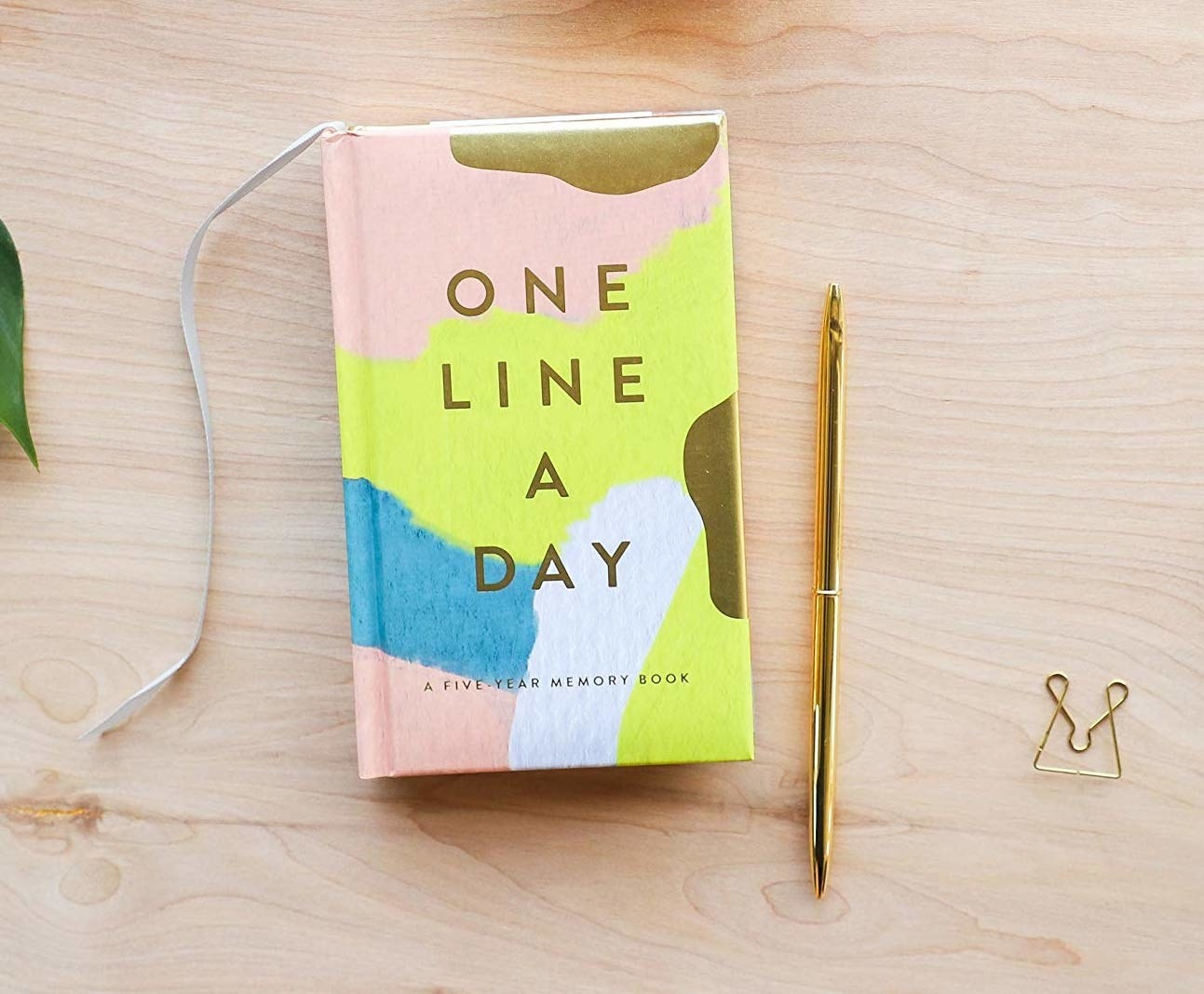 the one line a day journal with a pink, yellow, blue, and gold painted cover