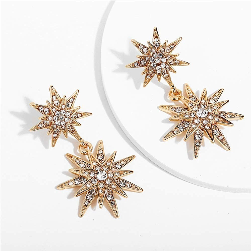 The gold tone earrings, one star on the lobe and one star dangling