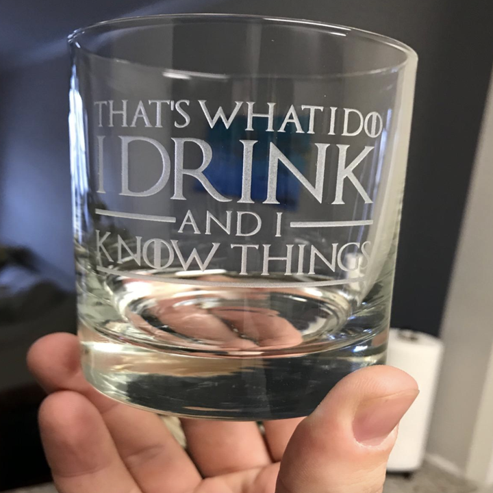 """reviewer holding the clear glass with text """"That's what I do, I drink and I know things"""""""