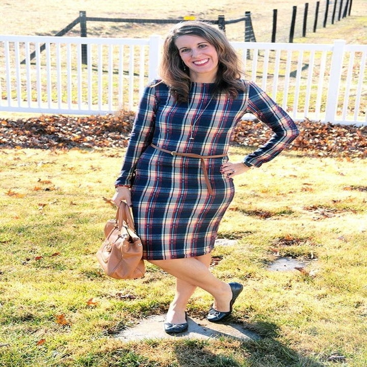 Reviewer wearing the knee-length blue, white, and red plaid bodycon dress