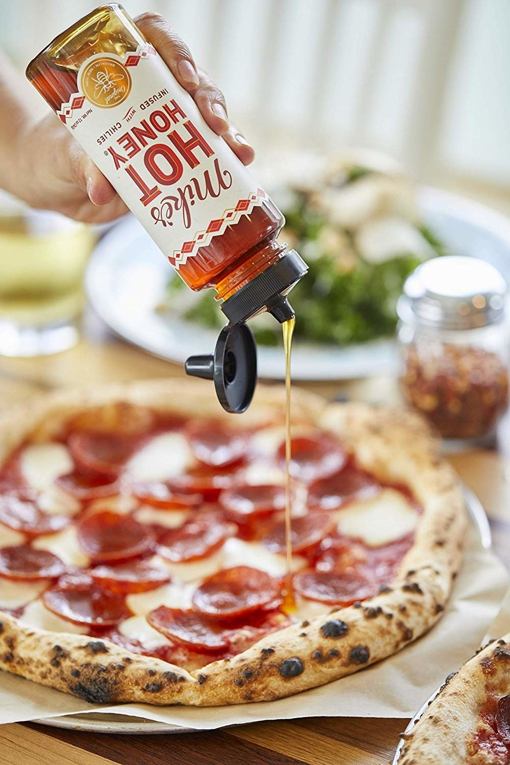 Someone pouring Mike's Hot Honey on a pizza.