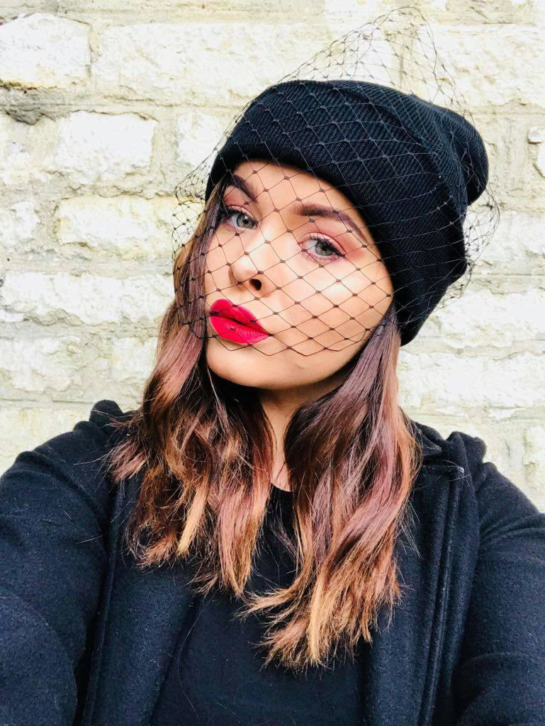 Model in the black beanie with a veil that hangs over part of their face