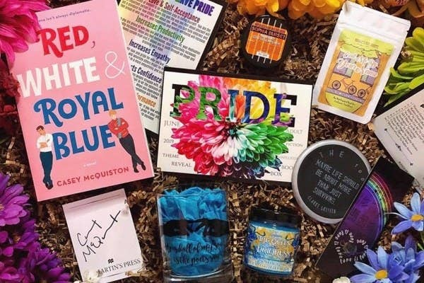 """""""Red, White & Royal Blue"""" book along with a candle, tea package, a cup, and other items"""