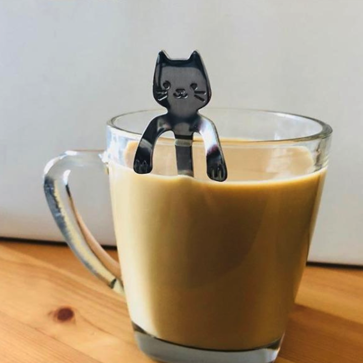 the cat spoon sitting inside of a clear mug of coffee