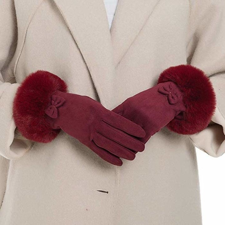 model wearing burgundy gloves with fur around the wrists and a bow