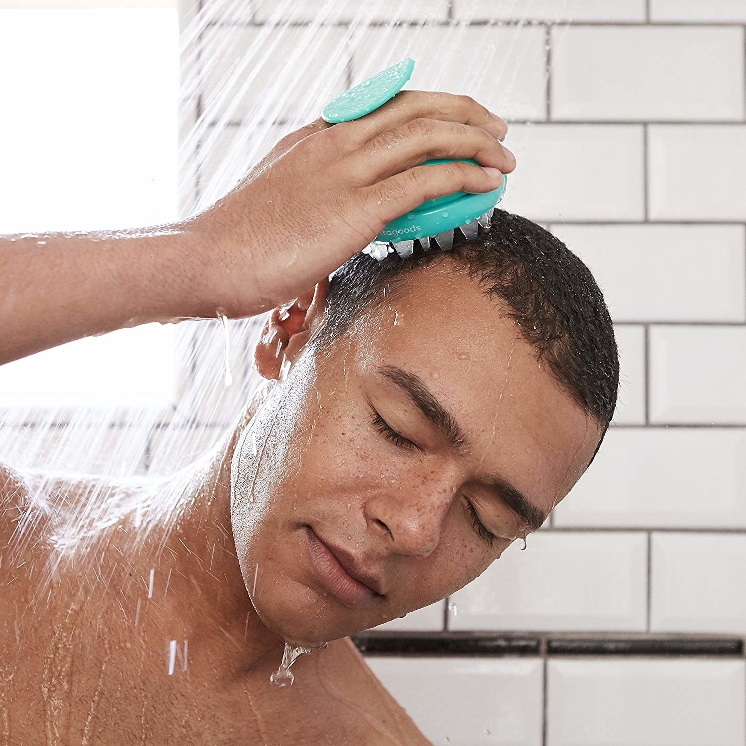 A person using the vibrating head massager under the shower