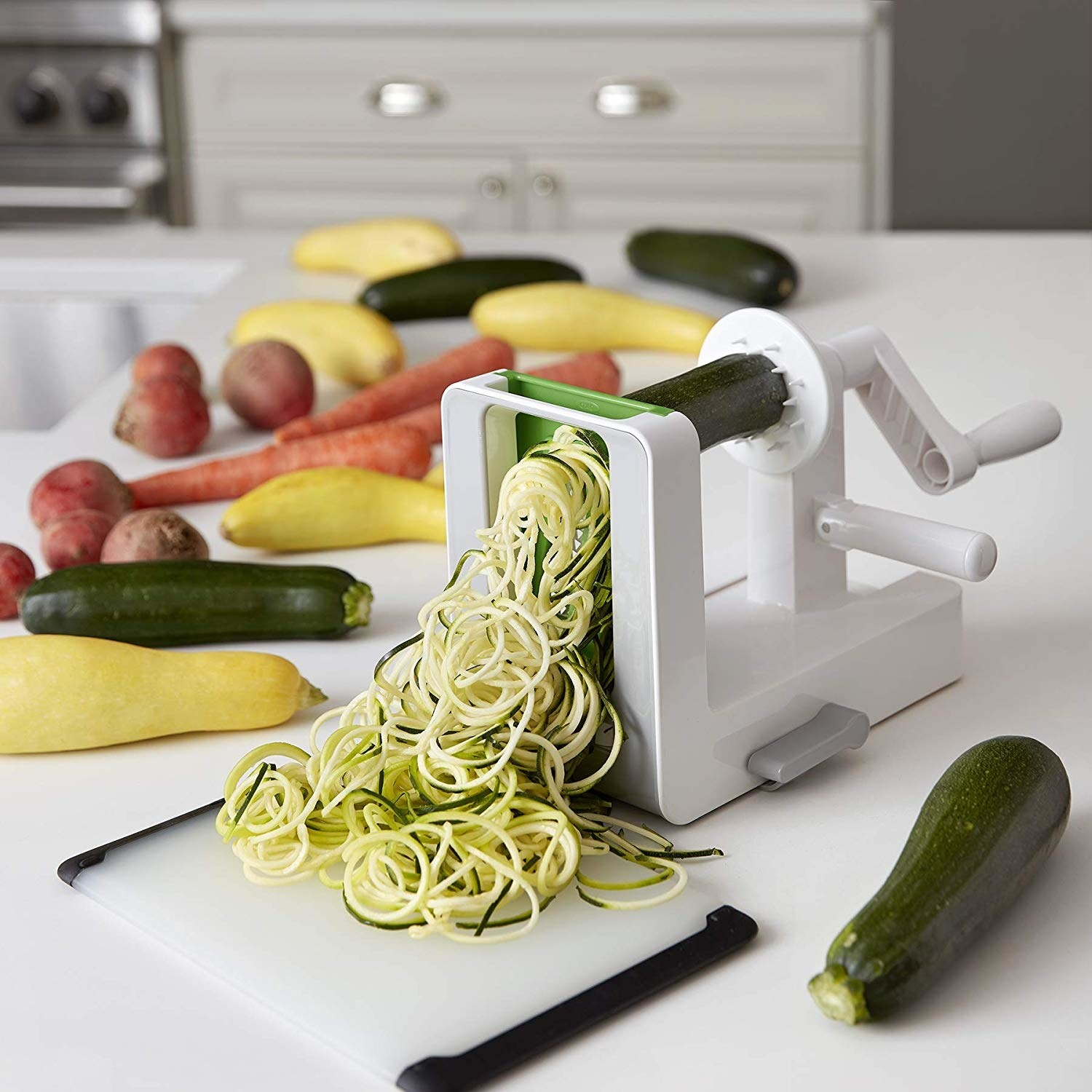 A zucchini being turn into curly noodles using a spiralizer machine