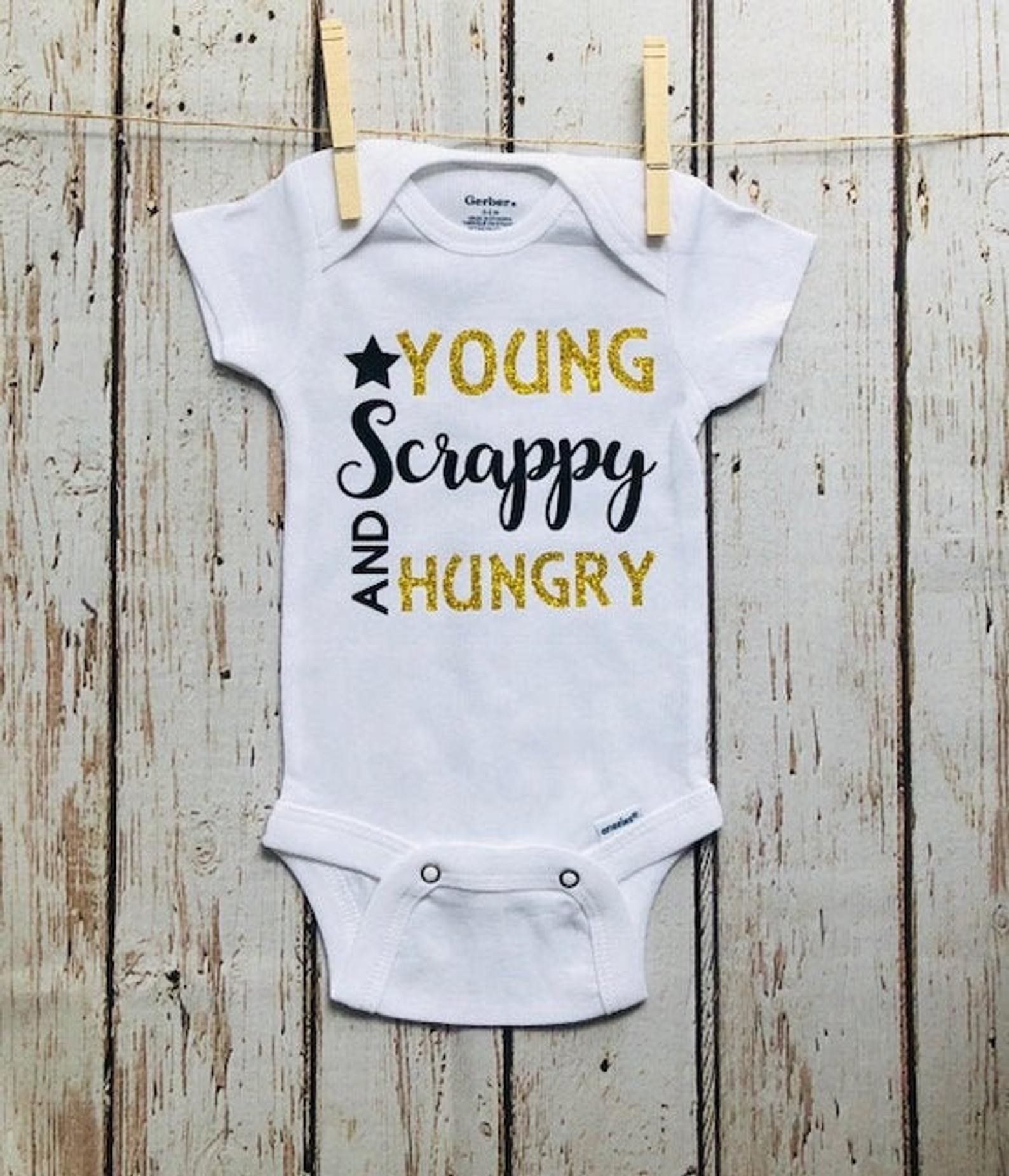 A white short-sleeved onesie with young scrappy and hungry written on it in black and gold
