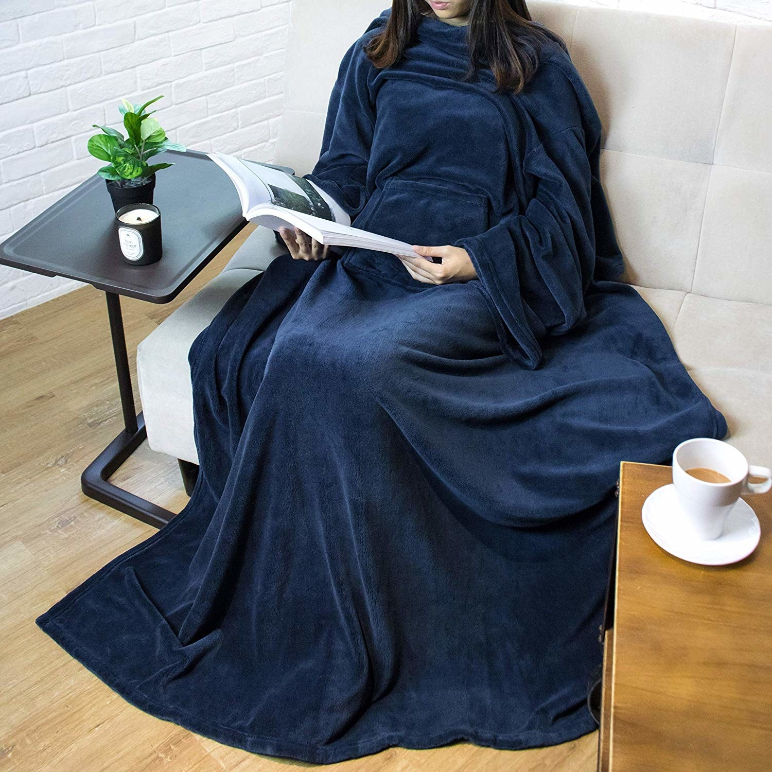 a person sitting on a couch wearing the fleece blanket in navy