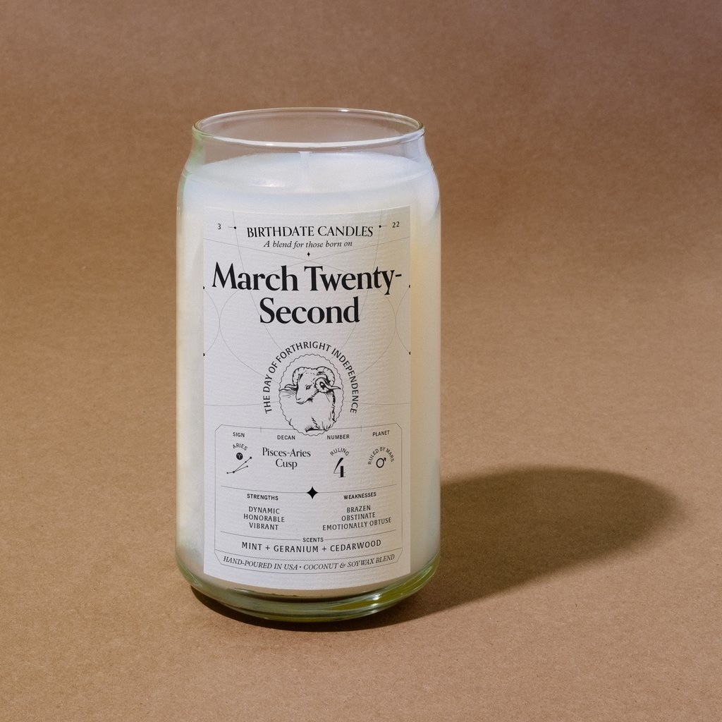candle in clear glass container with astrological information for march twenty-second