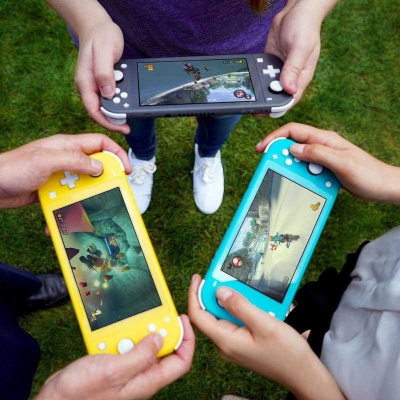 three pairs of hands holding yellow, teal, and black nintendo switch lites