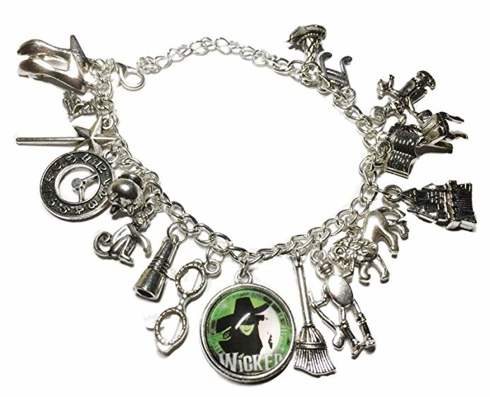 The silver bracelet with a lot of assorted charms related to the musical Wicked, including a broom, glasses, clock, want, and more, plus a green charm with the logo for the show