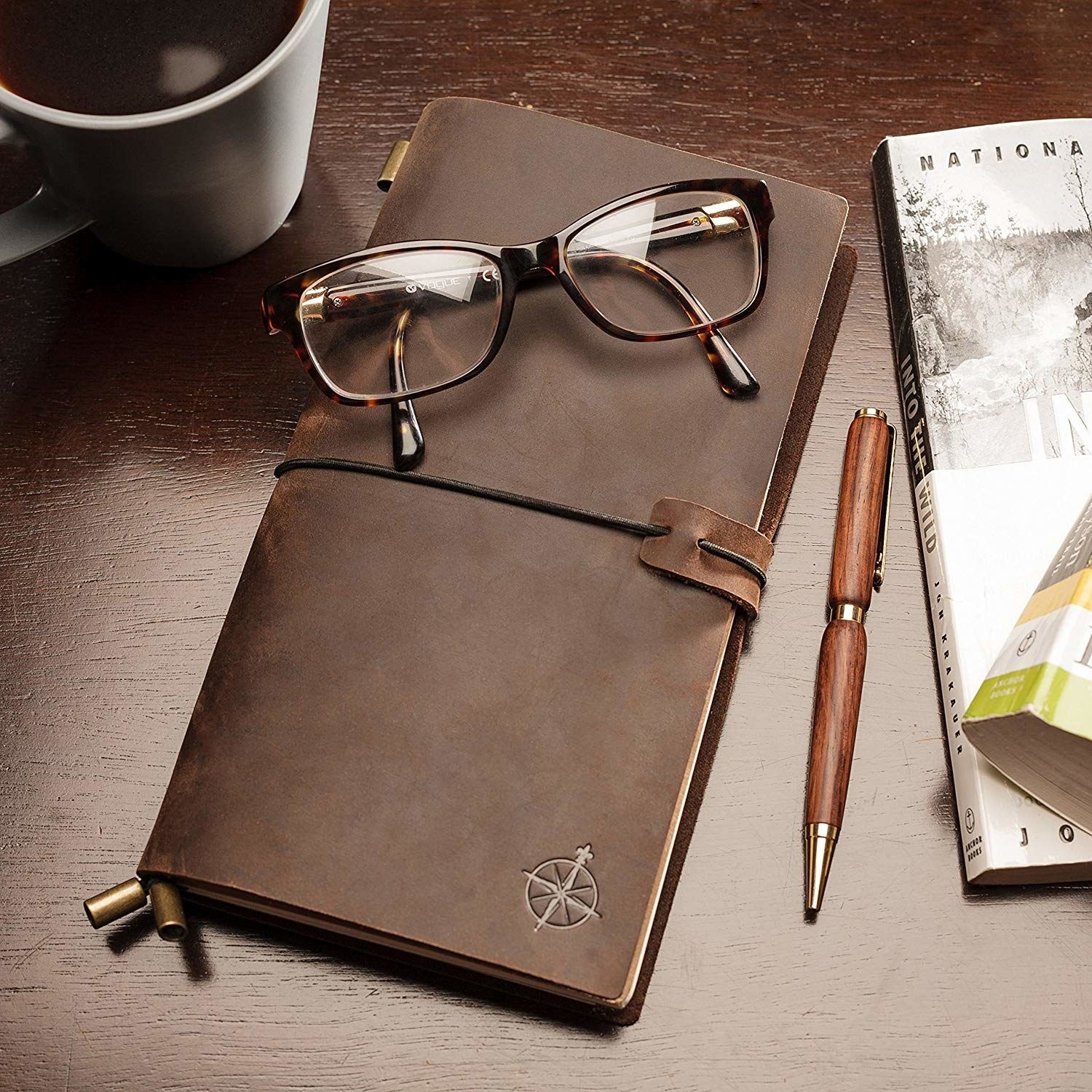 The leather notebook on a desk with a pair of glasses and an elegant pen