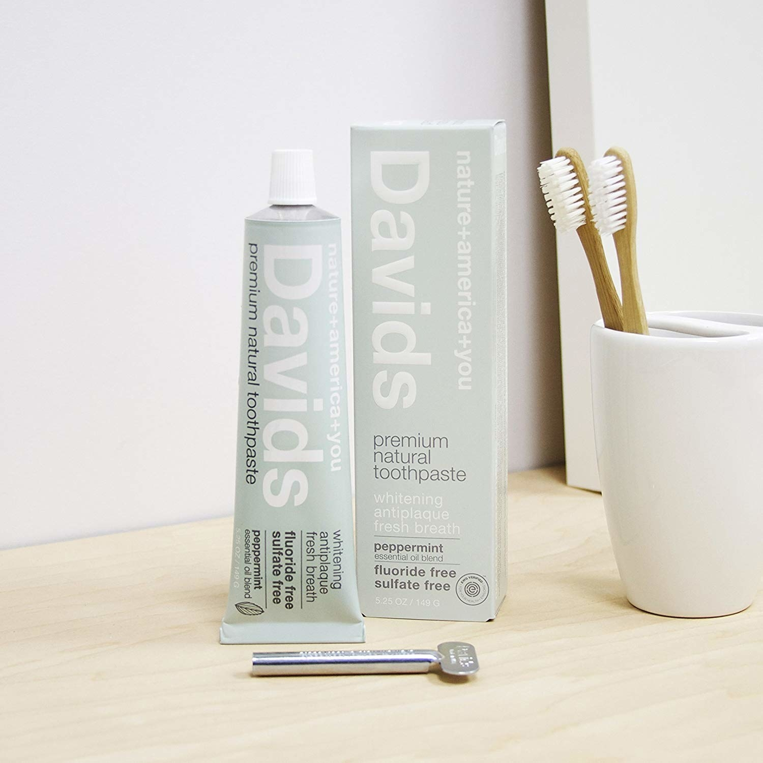 Product shot of the toothpaste in mint green packaging with clear white writing