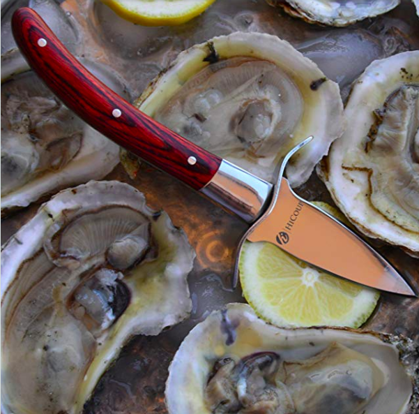 An oyster shucker with a wooden handle on a bed of shucked oysters