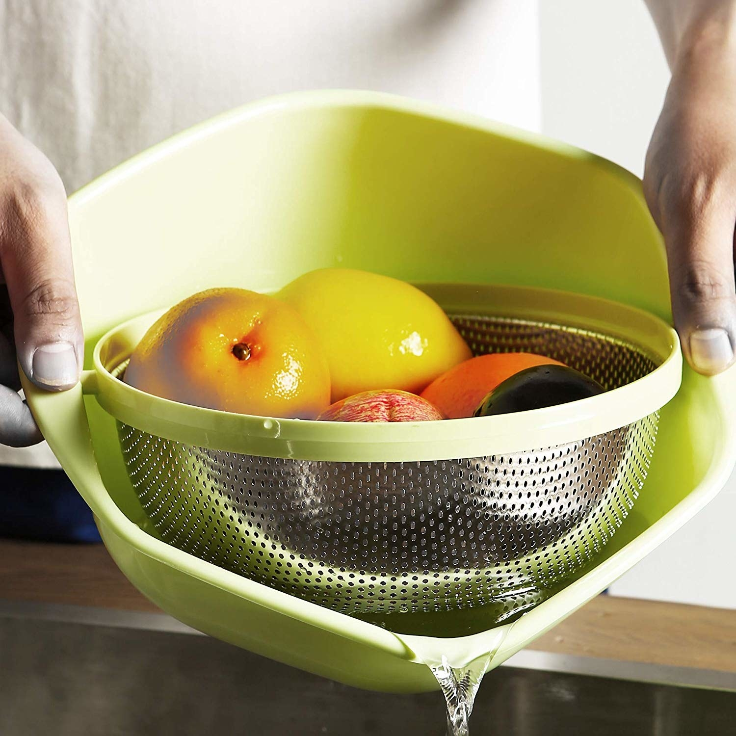 The green bowl with metal colander suspended inside, with fruit being washed inside of it