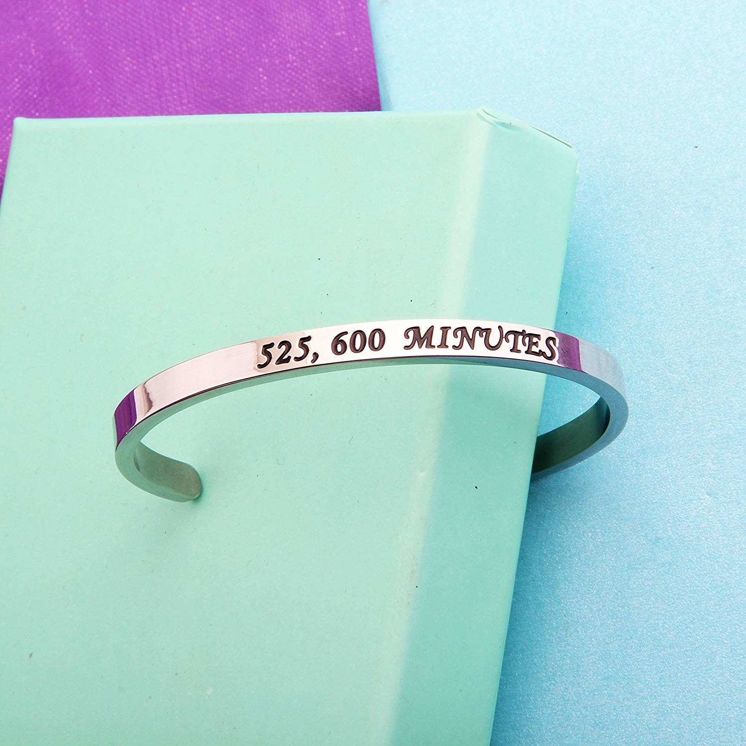 """A silver bangle with """"525,000 minutes"""" engraved in it"""