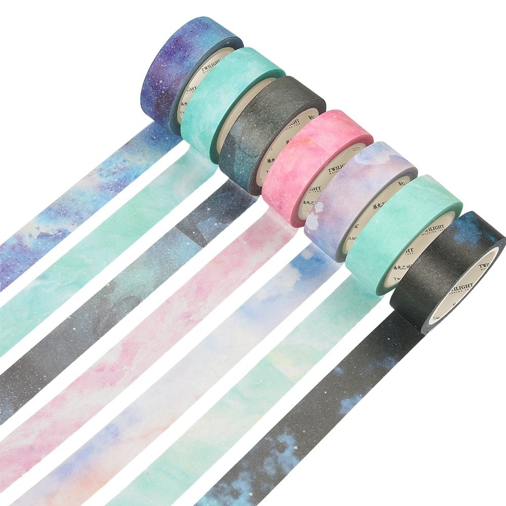 Seven rolls of washi tape on a plain background