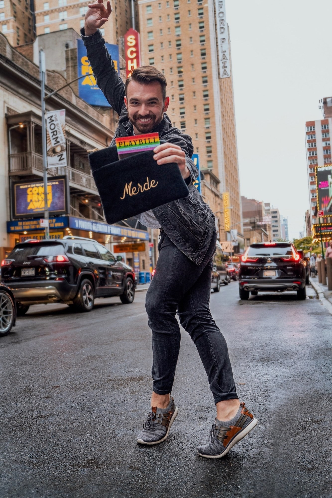 "Model holding the black velvet rectangle bag with the word ""Merde"" written in gold with a pocket on the front"