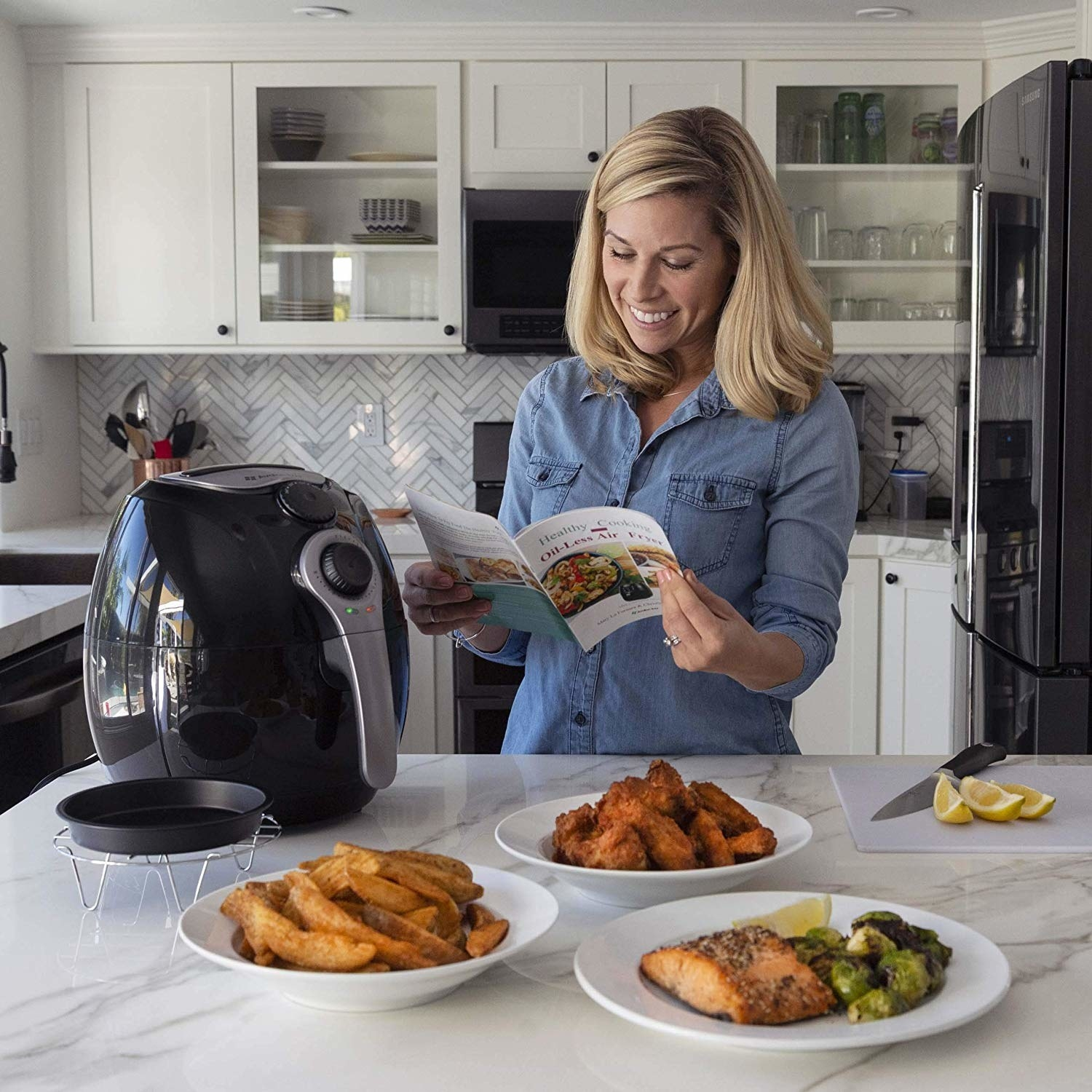 Model looking at the air fryer, reading the guide, with plates of air fried fries, wings, and salmon and brussels sprouts on the counter
