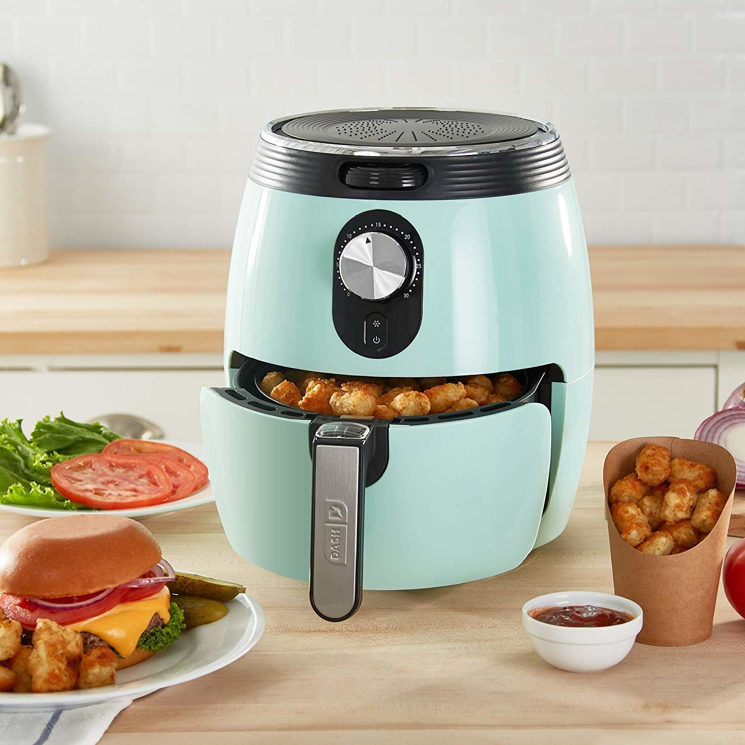 The light blue air fryer with basket filled with tater tots