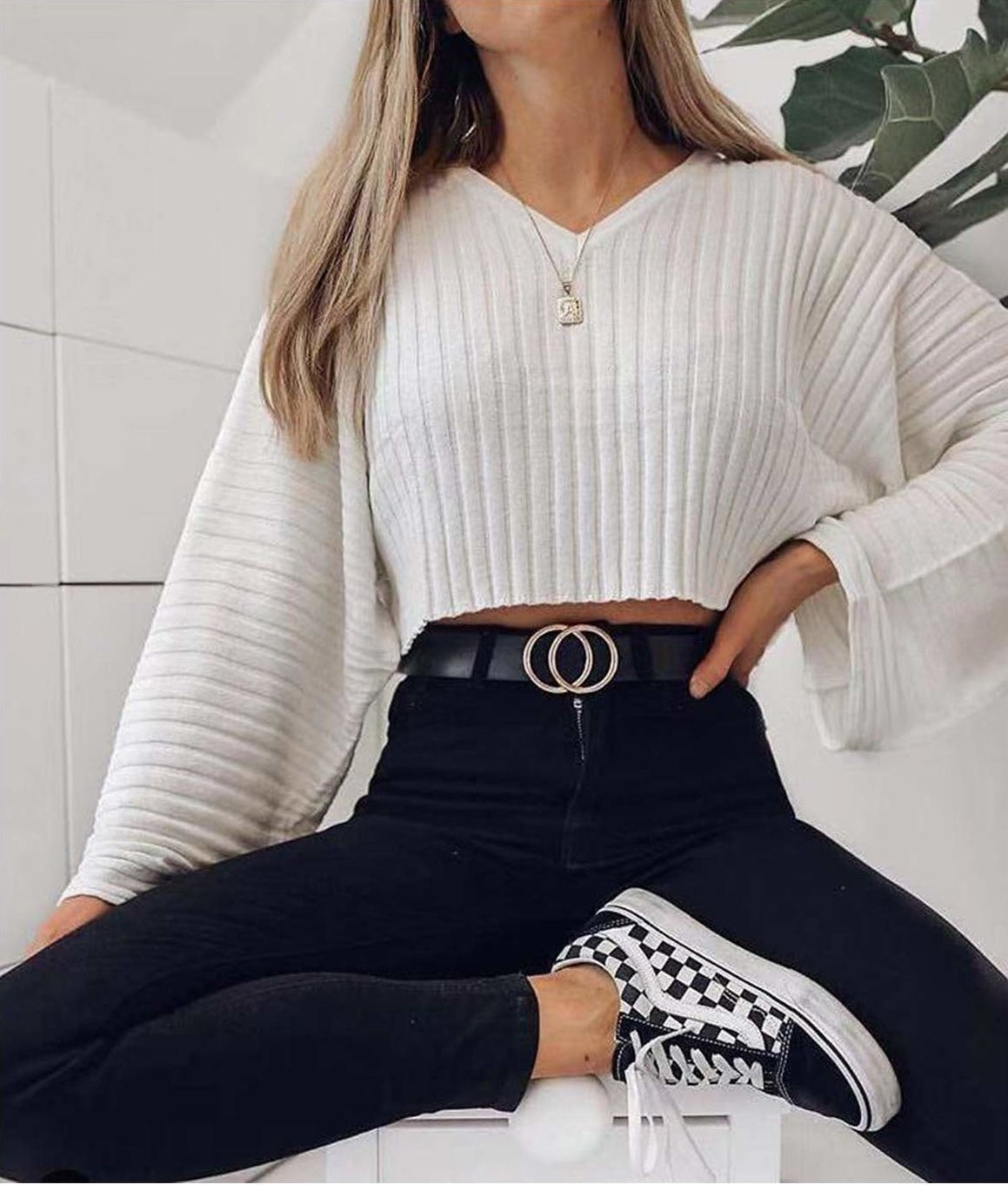 A person sitting with their hand on their hip They are wearing a long sleeved shirt, jeans, and a belt with a buckle in the shape of two interlocked circles